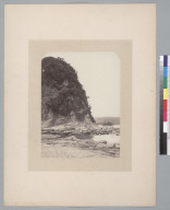 Large outcropping near rocky shore, pier in distance. [photographic print]