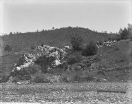 Man sitting on rock outcropping, Louise Mine. [transparency]