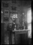 [Small table displaying portraits, flowers, and other items.] [negative]