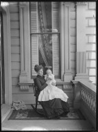 Carrie [Mrs. William Letts] Oliver holding baby Albert Leslie on porch. [negative]