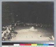 Night scene of members gathered around campfire, hand holding camera at lower corner, Bohemian Grove. [photographic print]