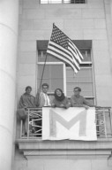 Students on Sproul Hall balcony with flag.