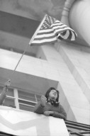 Student with American flag on Sproul Hall balcony.