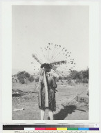 Performer wearing skirt of frayed willow bark, flicker-feather headbands and headdress of wands tipped with California poppies, Big Head Dance