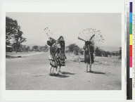 Three performers: two with red caps and cloth skirts, one with bark and flicker-feather headbands, Big Head Dance