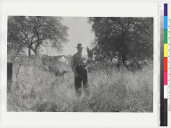 """View of """"Ishi Site;"""" man in checkered shirt standing in field, house in background"""