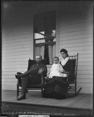 Clarence DeCamp and family (wife and child) on porch, Caspar Creek, Mendocino County, California. [negative]