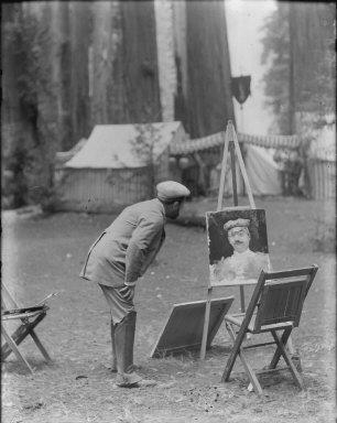 Man looking at portrait, Bohemian Grove. [negative]