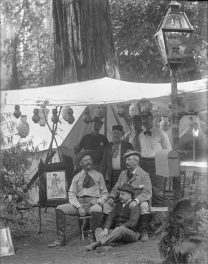 Group portrait of seven men outside tent, lamppost in foreground, Bohemian Grove. [negative]