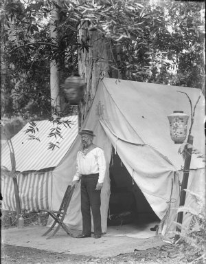 """Man wearing straw hat and """"sailor top,"""" standing by tent, Bohemian Grove. [negative]"""