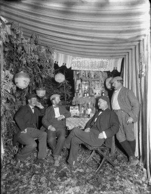 Four men at bar in tent, Bohemian Grove. [transparency]