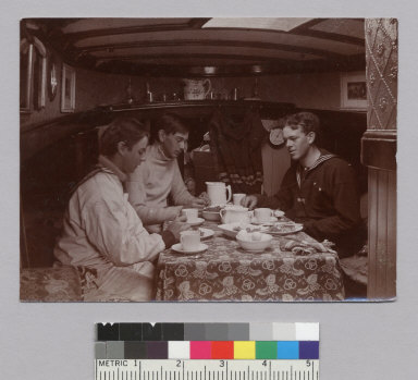 Three young men eating in galley of yacht. [photographic print]